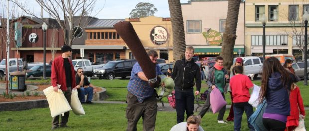 Zac Shank wields his pillow weapon above his head moving toward a fellow pillow fighter. Photo by   Curran Daly